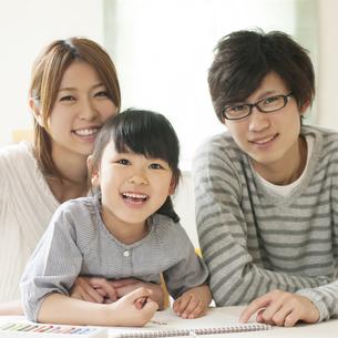 お絵描きをする女の子と両親の写真素材 [FYI04555494]