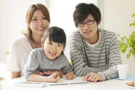 お絵描きをする女の子と両親の写真素材 [FYI04555495]