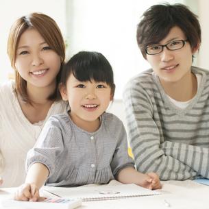 お絵描きをする女の子と両親の写真素材 [FYI04555496]
