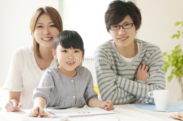お絵描きをする女の子と両親の写真素材 [FYI04555497]