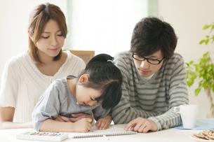 お絵描きをする女の子と両親の写真素材 [FYI04555498]