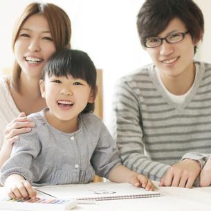 お絵描きをする女の子と両親の写真素材 [FYI04555499]
