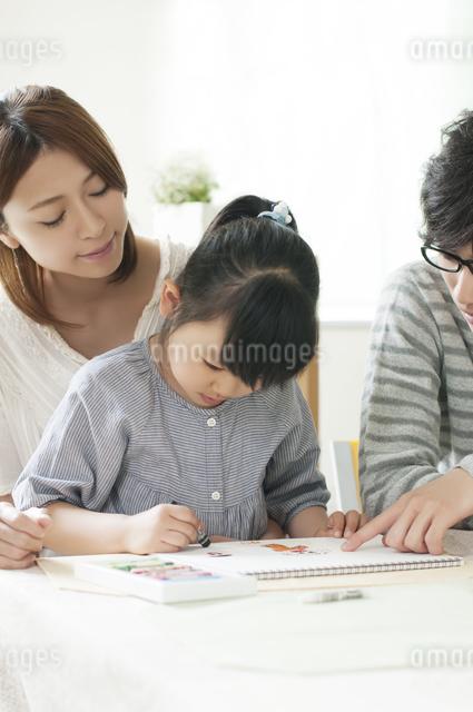 お絵描きをする女の子と両親の写真素材 [FYI04555500]