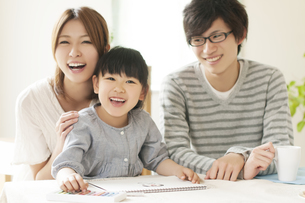 お絵描きをする女の子と両親の写真素材 [FYI04555501]