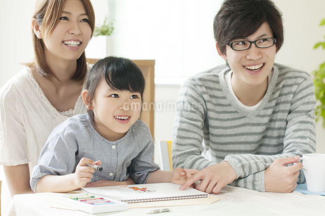 お絵描きをする女の子と両親の写真素材 [FYI04555503]