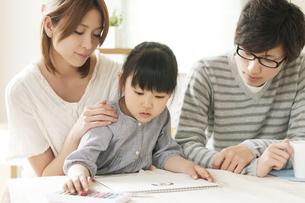 お絵描きをする女の子と両親の写真素材 [FYI04555504]