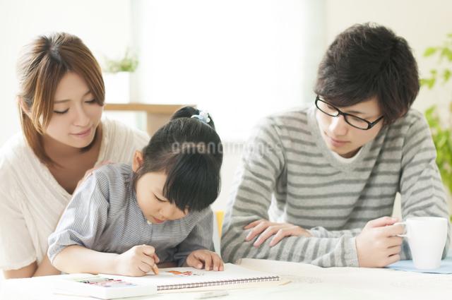 お絵描きをする女の子と両親の写真素材 [FYI04555505]