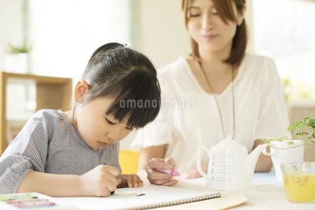 お絵描きをする女の子と母親の写真素材 [FYI04555507]