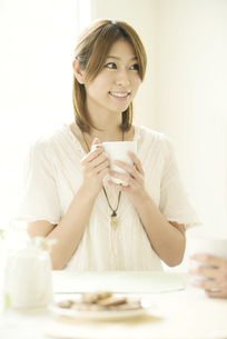 コーヒーカップを持ち微笑む女性の写真素材 [FYI04555521]