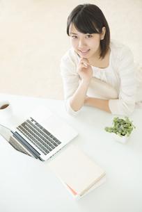 頬杖をつき微笑む女性の写真素材 [FYI04555676]