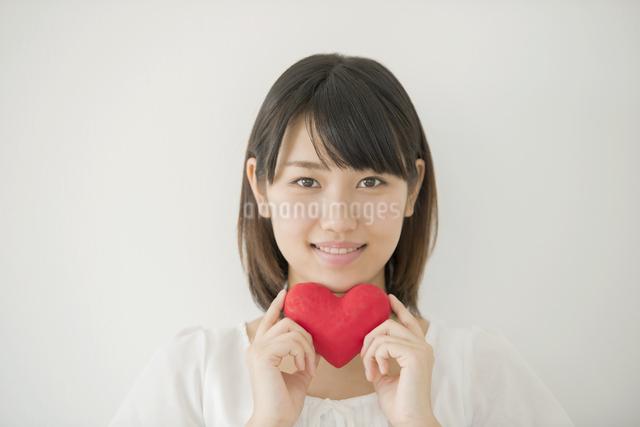 ハートを持ち微笑む女性の写真素材 [FYI04555705]