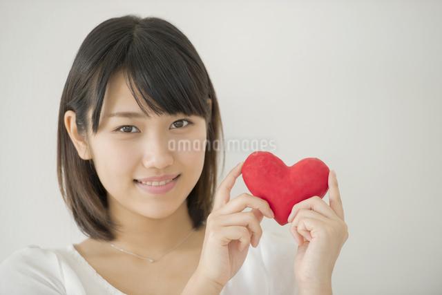 ハートを持ち微笑む女性の写真素材 [FYI04555706]