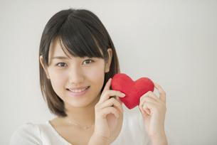 ハートを持ち微笑む女性の写真素材 [FYI04555707]