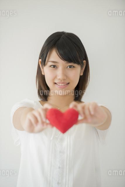 ハートを持ち微笑む女性の写真素材 [FYI04555710]