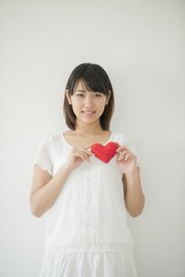 ハートを持ち微笑む女性の写真素材 [FYI04555711]