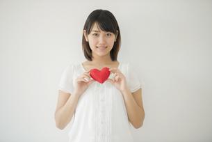 ハートを持ち微笑む女性の写真素材 [FYI04555712]