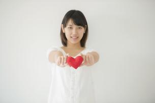 ハートを持ち微笑む女性の写真素材 [FYI04555713]