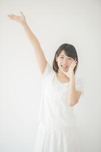 片手を挙げ微笑む女性の写真素材 [FYI04555718]