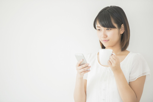 コーヒーカップを持ちスマートフォンを操作する女性の写真素材 [FYI04555727]