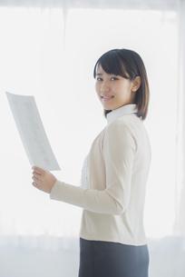 書類を持ち微笑むビジネスウーマンの写真素材 [FYI04555760]