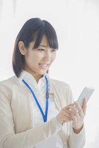 スマートフォンを操作するビジネスウーマンの写真素材 [FYI04555764]