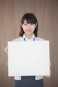 メッセージボードを持ち微笑むビジネスウーマンの写真素材 [FYI04555785]