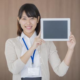 タブレットPCを持ち微笑むビジネスウーマンの写真素材 [FYI04555788]