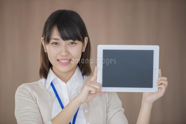 タブレットPCを持ち微笑むビジネスウーマンの写真素材 [FYI04555792]