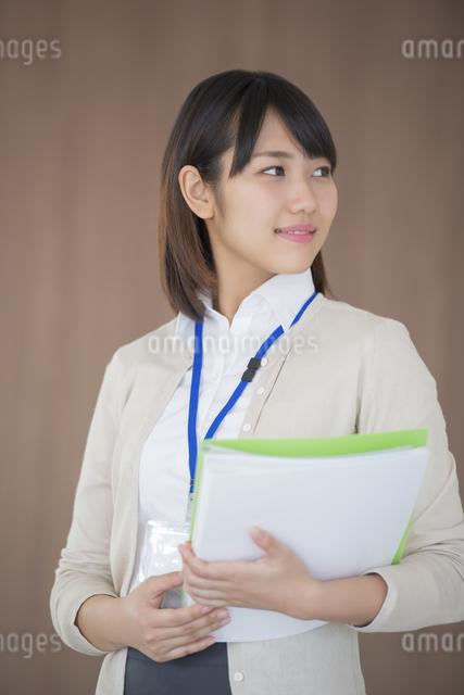 ファイルを持ち微笑むビジネスウーマンの写真素材 [FYI04555797]