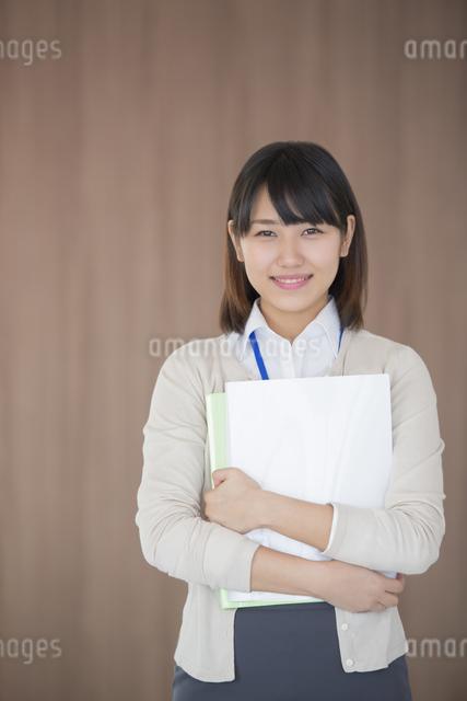 ファイルを持ち微笑むビジネスウーマンの写真素材 [FYI04555801]