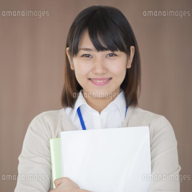 ファイルを持ち微笑むビジネスウーマンの写真素材 [FYI04555803]