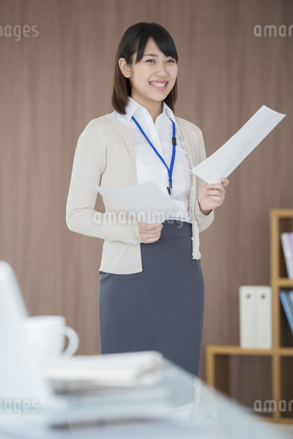 書類を持ち微笑むビジネスウーマンの写真素材 [FYI04555809]