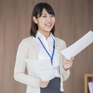 書類を持ち微笑むビジネスウーマンの写真素材 [FYI04555810]