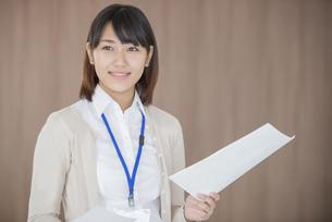 書類を持ち微笑むビジネスウーマンの写真素材 [FYI04555827]