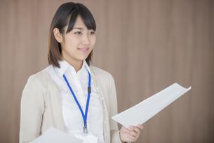 書類を持ち微笑むビジネスウーマンの写真素材 [FYI04555828]
