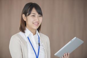 タブレットPCを持ち微笑むビジネスウーマンの写真素材 [FYI04555829]