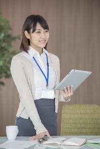 タブレットPCを持ち微笑むビジネスウーマンの写真素材 [FYI04555830]