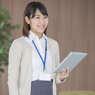 タブレットPCを持ち微笑むビジネスウーマンの写真素材 [FYI04555832]
