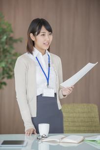 書類を持ち微笑むビジネスウーマンの写真素材 [FYI04555834]
