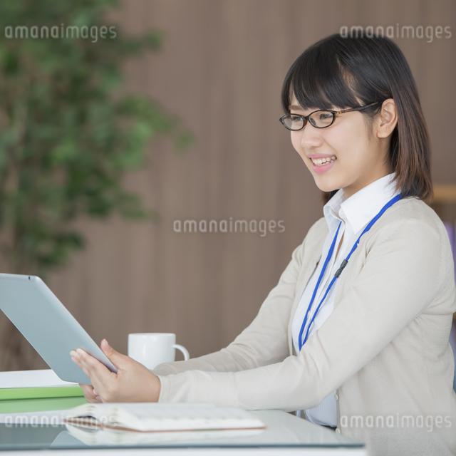 タブレットPCを操作するビジネスウーマンの写真素材 [FYI04555843]