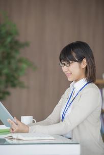 タブレットPCを操作するビジネスウーマンの写真素材 [FYI04555844]