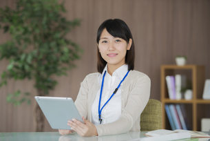タブレットPCを持ち微笑むビジネスウーマンの写真素材 [FYI04555847]