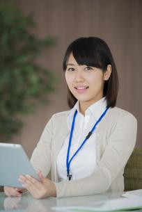 タブレットPCを持ち微笑むビジネスウーマンの写真素材 [FYI04555850]