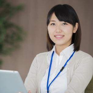 タブレットPCを持ち微笑むビジネスウーマンの写真素材 [FYI04555852]