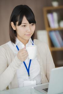 オフィスでコーヒーを飲むビジネスウーマンの写真素材 [FYI04555886]