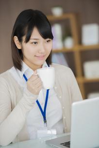 オフィスでコーヒーを飲むビジネスウーマンの写真素材 [FYI04555887]