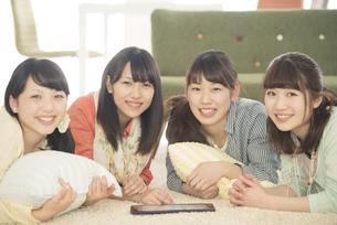 床に寝転び微笑む4人の女性の写真素材 [FYI04555902]