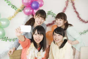 スマートフォンで自分撮りをする4人の女性の写真素材 [FYI04555970]