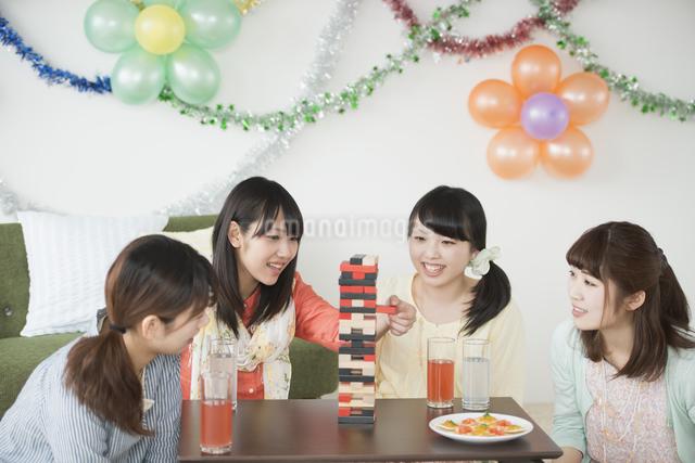 ジェンガで遊ぶ4人の女性の写真素材 [FYI04556012]