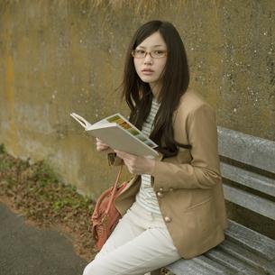 ベンチに座り本を読む女性の写真素材 [FYI04556042]